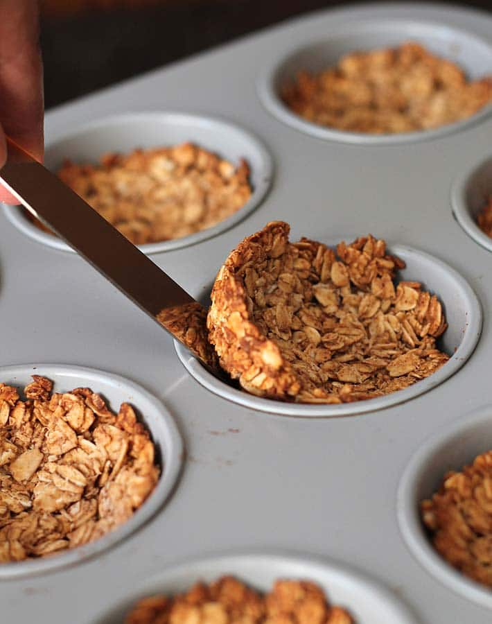 Freshly baked granola cups in a muffin pan, one granola cup is being removed with an icing spatula.