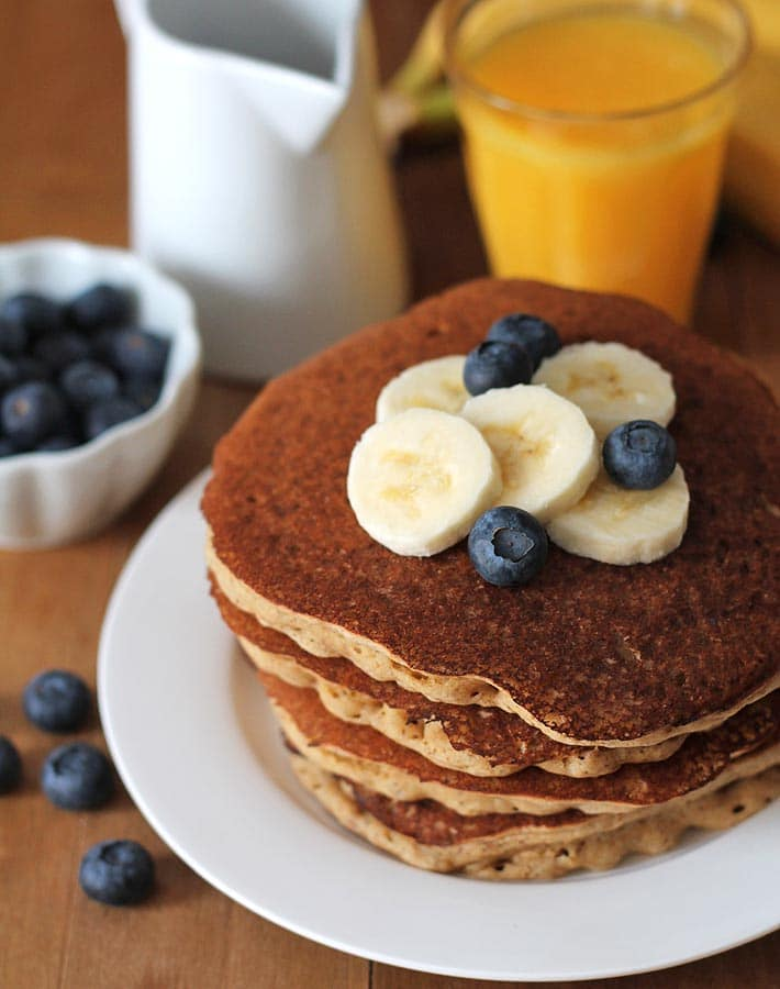 A stack of four Vegan Banana Pancakes sitting on a white plate, pancakes are garnished with fresh sliced bananas and fresh blueberries, a glass of orange juice sits behind the plate and two bananas sit behind the plate off to the right.