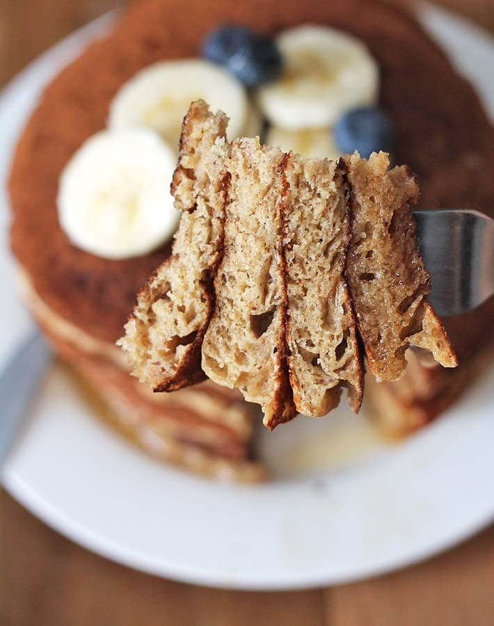A close up shot of a sliced cross section of four Vegan gluten free Banana Pancakes on a fork to show how fluffy the inside of the pancakes are.