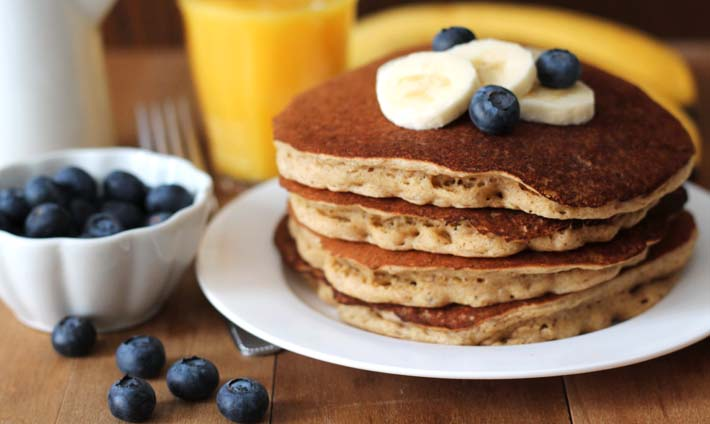 Four Vegan Banana Pancakes on a white plate sitting on a light brown wooden table, pancakes are garnished with fresh bananas and blueberries; a small white cup of fresh blueberries sits to the left of the plate.