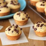 Four Mini Chocolate Chip Muffins sitting on individual parchment paper squares on a brown wooden table.