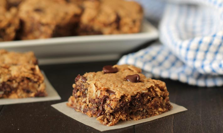 Chocolate Chip Peanut Butter Oatmeal Bars on a white plate in the background, one bar is in the foreground on a parchment paper square and a blue and white cloth sits to the right in the background.