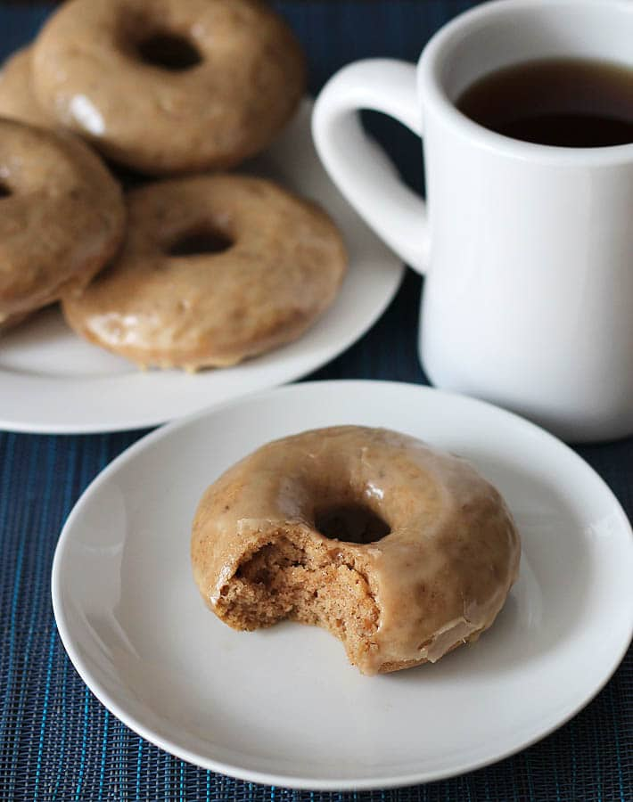 A stack of Vegan Gluten Free Maple Doughnuts on a white plate in the background, a smaller plate is at the forefront with a doughnut on it, the doughnut has a bite taken out of it, a cup of coffee sits in the background on the right.