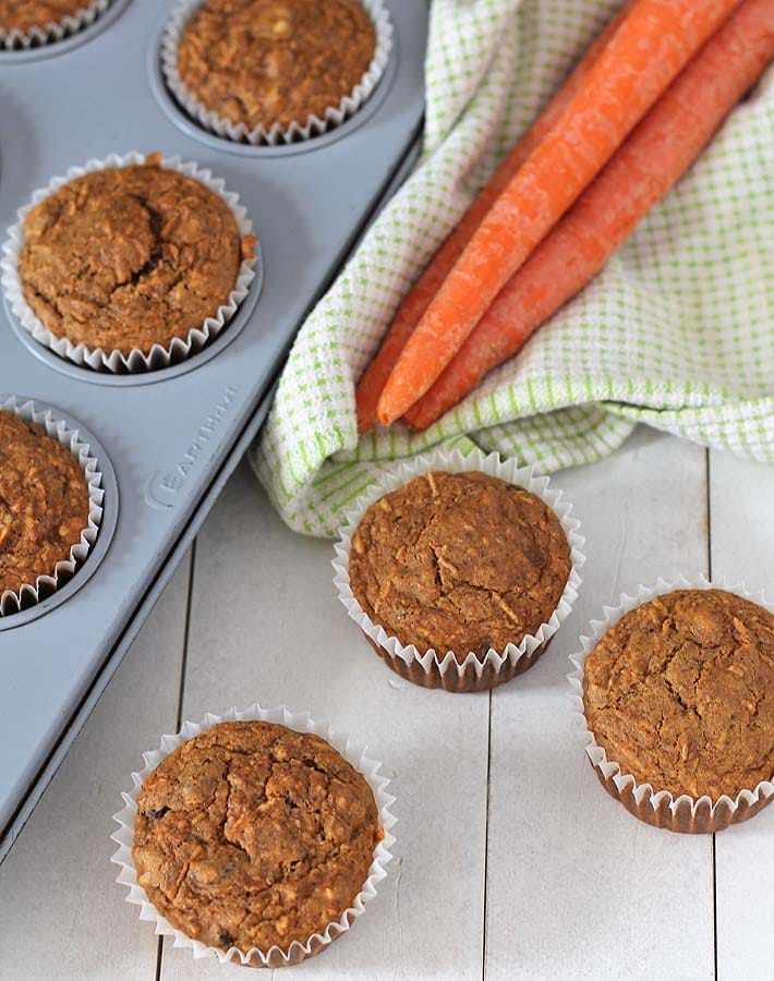 Vegan carrot muffins on a white wooden table, a muffin pan of muffins sits to the left and a green tea towel with three raw carrots are on top of the towel.