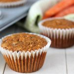 Three vegan carrot muffins sitting on a white wood table, a pan of muffins sits to the left and a green kitchen cloth with three fresh carrots on top of it sits in the background.