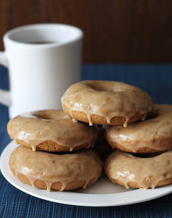 Vegan Gluten Free Maple Doughnuts stacked on top of each other on a white plate, a cup of coffee sits in the background on the left.