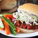 Lentil Sloppy Joes sandwich on a white plate, sandwich is topped with chopped cabbage, carrot and cucumber sticks also sit on the plate to the left.