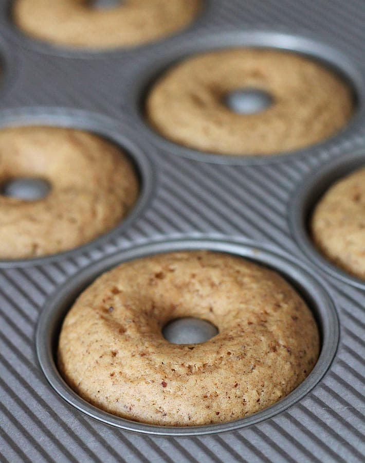 Fresh out of the oven Vegan Gluten Free Maple Doughnuts in a doughnut pan.