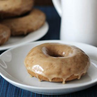 A plate of Vegan Gluten Free Maple Doughnuts sits on a blue place mat in the background on the left, in the foreground, one doughnut sits on a small white plate, a white cup sits off to the right in the background.