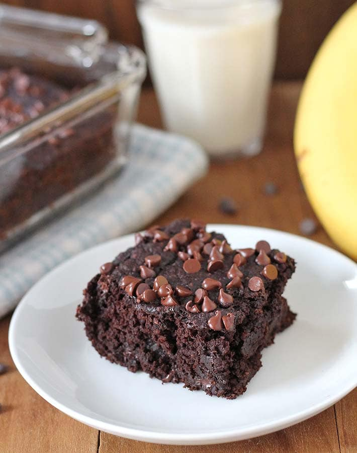 A square of vegan gluten-free chocolate banana cake on a white plate, a glass of almond milk sits in the background, a bunch of fresh bananas sits to the right, and the baking dish with the rest of the cake sits to the left.