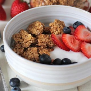 A bowl with peanut butter granola, yogurt, fresh strawberries and blueberries sitting on a white wooden table.