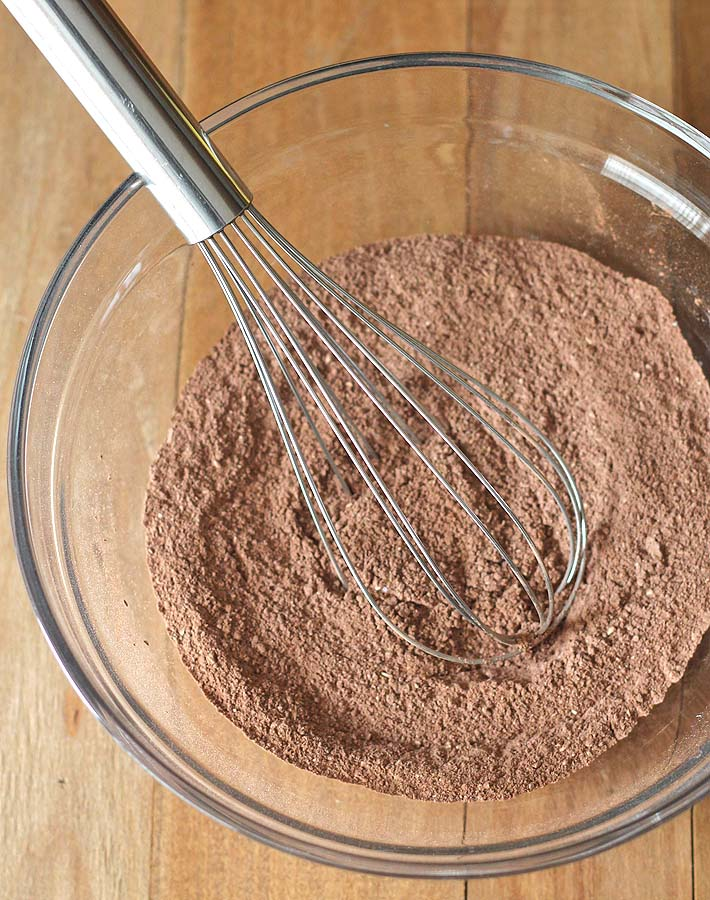The dry ingredients for vegan gluten-free chocolate banana cake in a glass bowl with a wire whisk sitting on the side of the bowl.