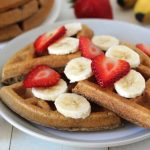 Vegan Banana Waffles on a white table in a white plate, waffles are garnished with sliced bananas and sliced strawberries.
