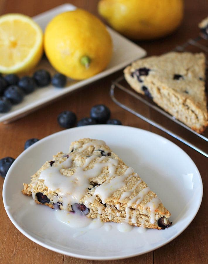 A glazed vegan gluten free Lemon Blueberry Scone sitting on a small white plate, more scones sit to the right on a cooling rack, fresh lemons and blueberries sit behind the plate.