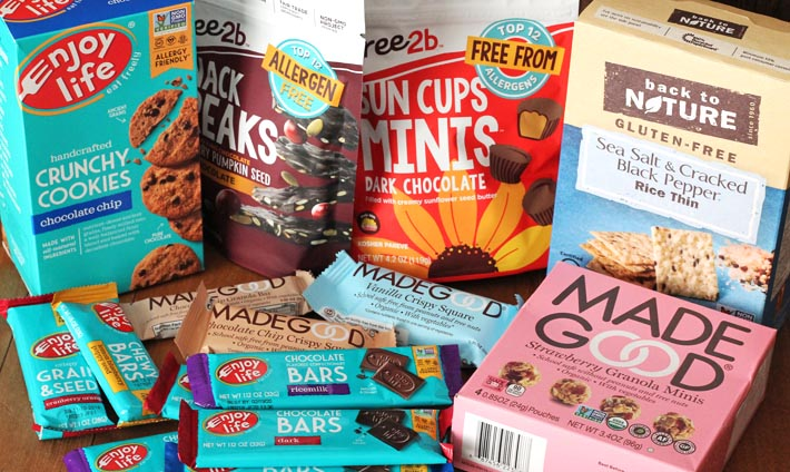 Several packages of packaged store-bought, allergy-friendly, nut-free snacks and treats sitting on a light brown wooden table.