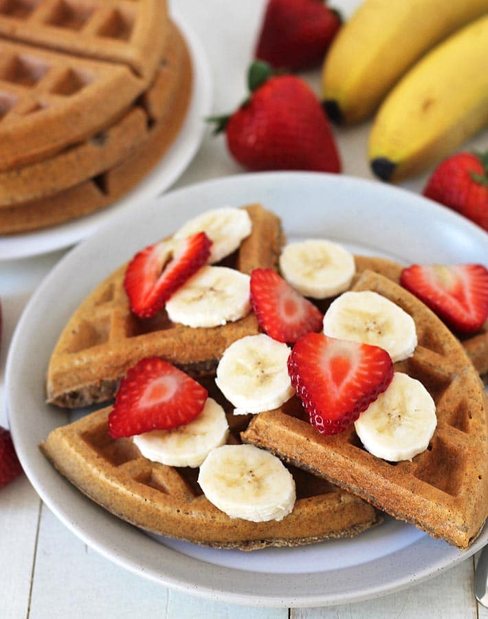 Close-up shot of Gluten-free Vegan Banana Waffles, plate of waffles is sitting on a white wooden table, the table has fresh bananas and strawberries on it as well as a small canister of maple syrup, a plate stacked with more waffles is sitting off to the left in the background.