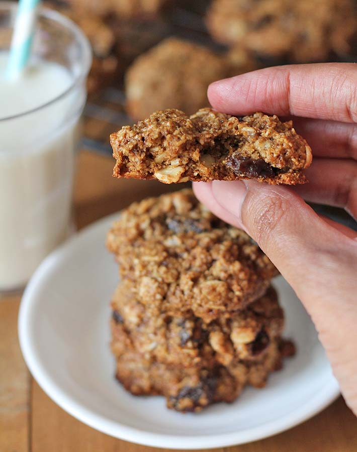 Vegan Oatmeal Raisin Cookies in the background, with a hand holding half of one of the cookies up close to show the soft inner texture.
