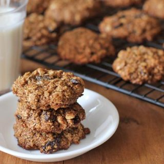 Three Vegan Oatmeal Raisin Cookies stacked on top of each other on a small white plate, a glass of almond milk with a blue straw sits in the background on the left and a cooling rack with the rest of the cookies sits in the background on the right.