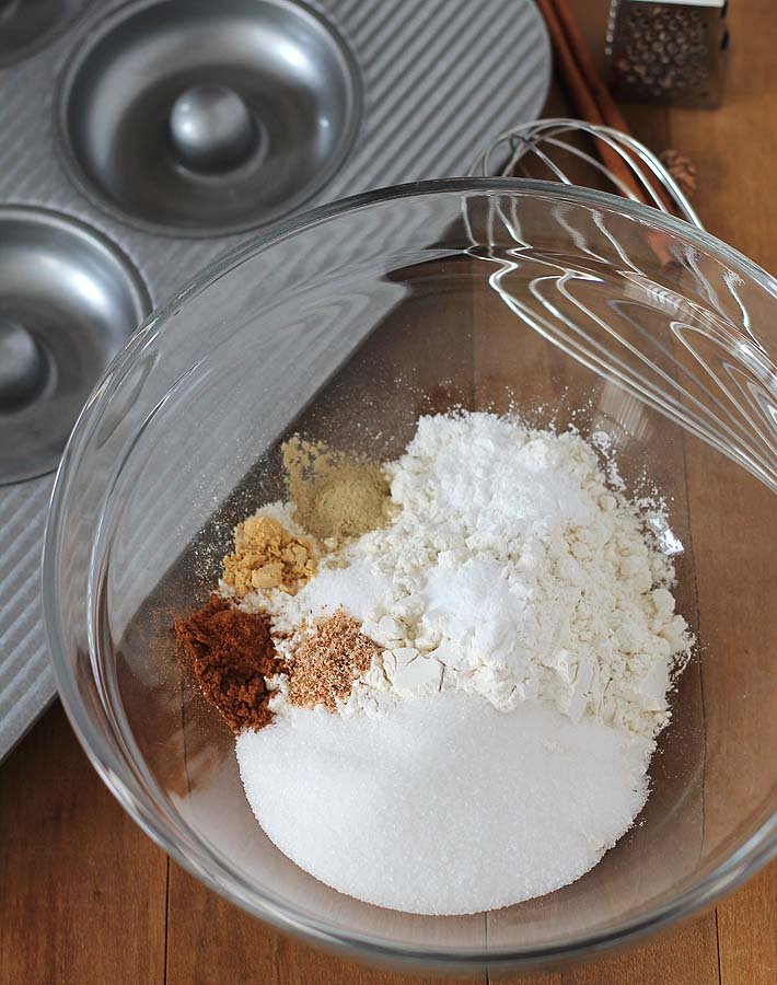 Overhead shot of the dry ingredients for Chai-Spiced Baked Vegan Doughnuts in a glass bowl, bowl is sitting on a wood table.
