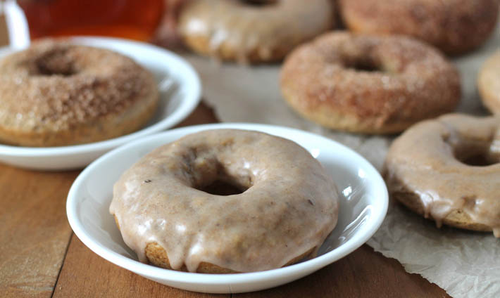 Chai-Spiced Baked Vegan Doughnuts on a wood table, two doughnuts are on white plates and the rest are on a crumpled piece of parchment paper.