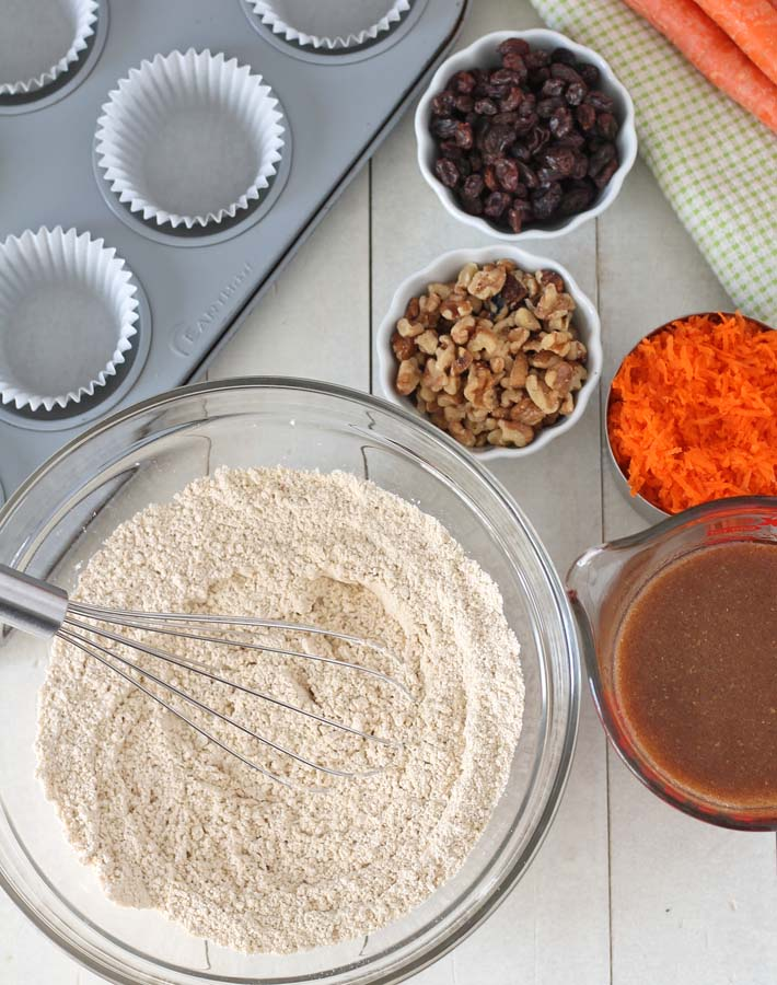 Overhead shot of the ingredients for vegan carrot muffins sitting on a white wooden table.