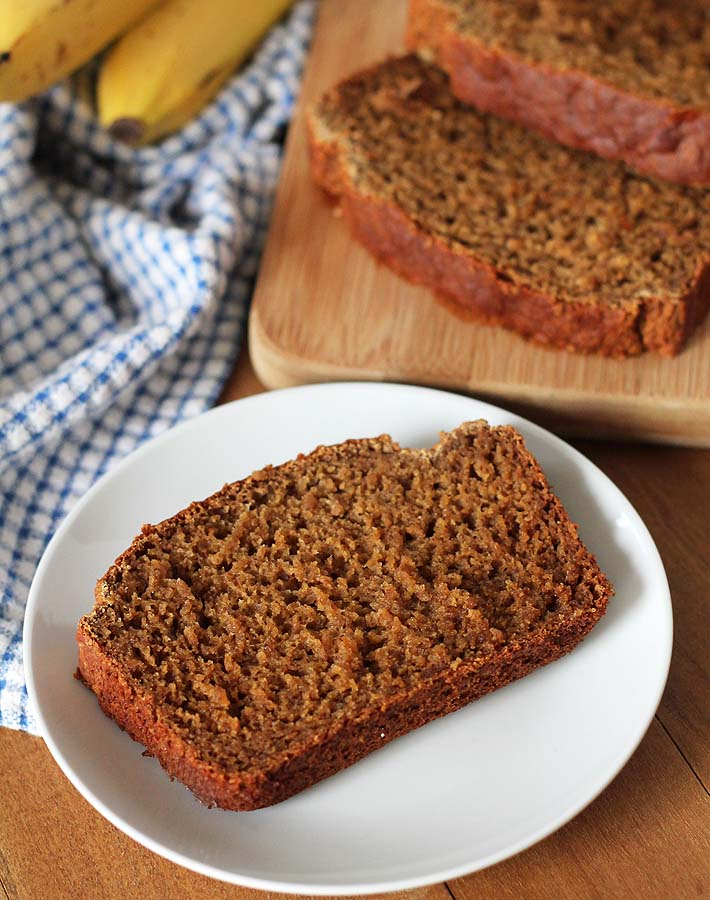 A slice of Vegan Gluten Free Banana Bread on a plate sitting on a brown wooden table, the rest of the sliced loaf is sitting behind the plate.
