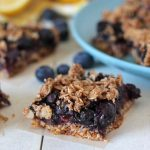 Blueberry Oatmeal Bars on a white table with fresh blueberries and lemons behind them.