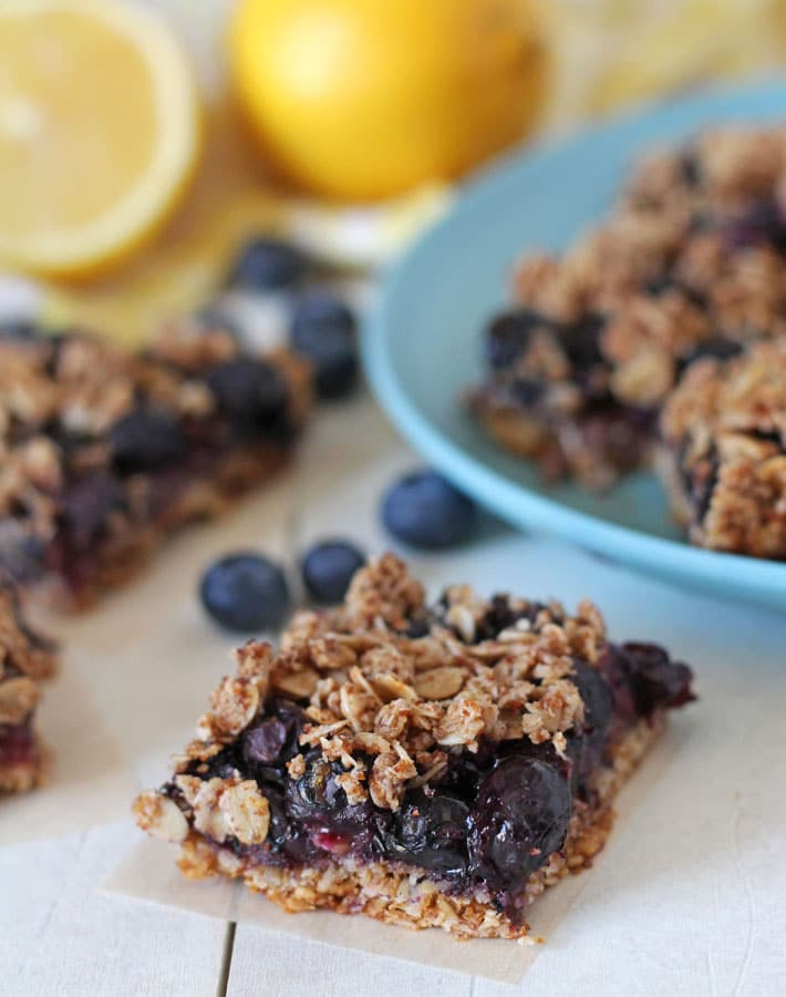 Blueberry Oatmeal Bars on a white tabletop, fresh lemons and blueberries sit behind the bars.