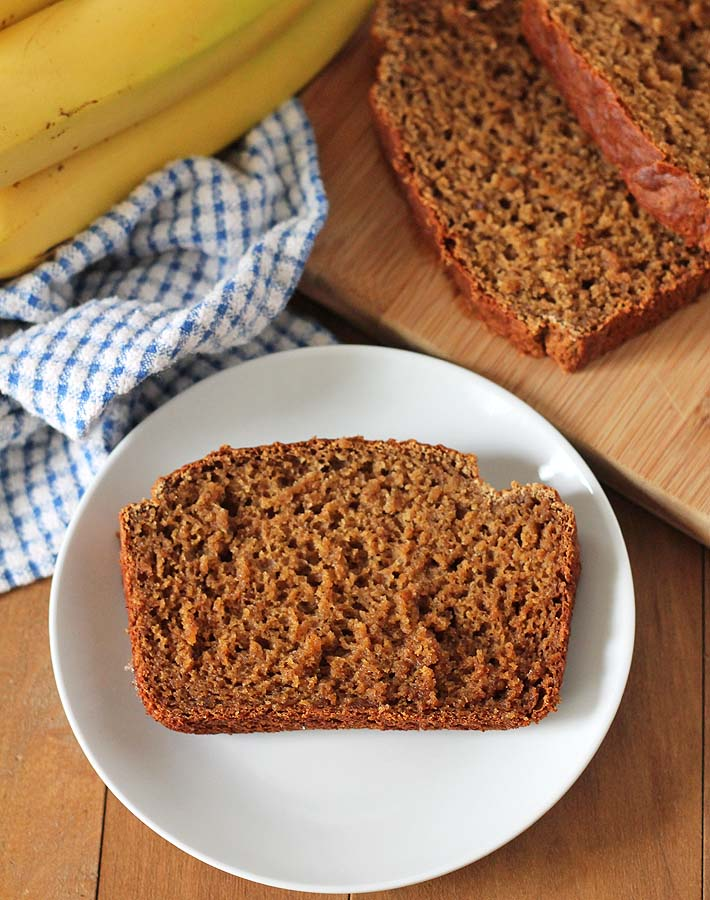 Overhead shot of a slice of Vegan Gluten Free Banana Bread on a plate, a bunch of bananas sits behind the plate on a blue and white dish cloth, the rest of the loaf sits to the right on a bamboo cutting board.