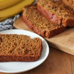A slice of Vegan Gluten Free Banana Bread on a small white plate, the rest of the bread sits behind the plate.