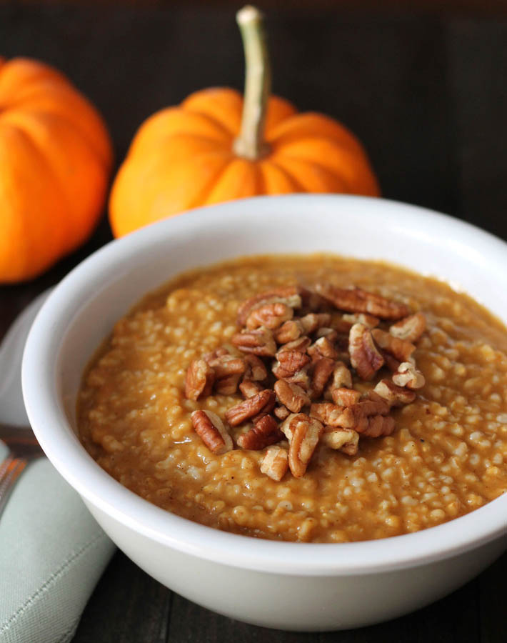 A bowl of Pumpkin Steel Cut Oats sitting on a dark wood table.