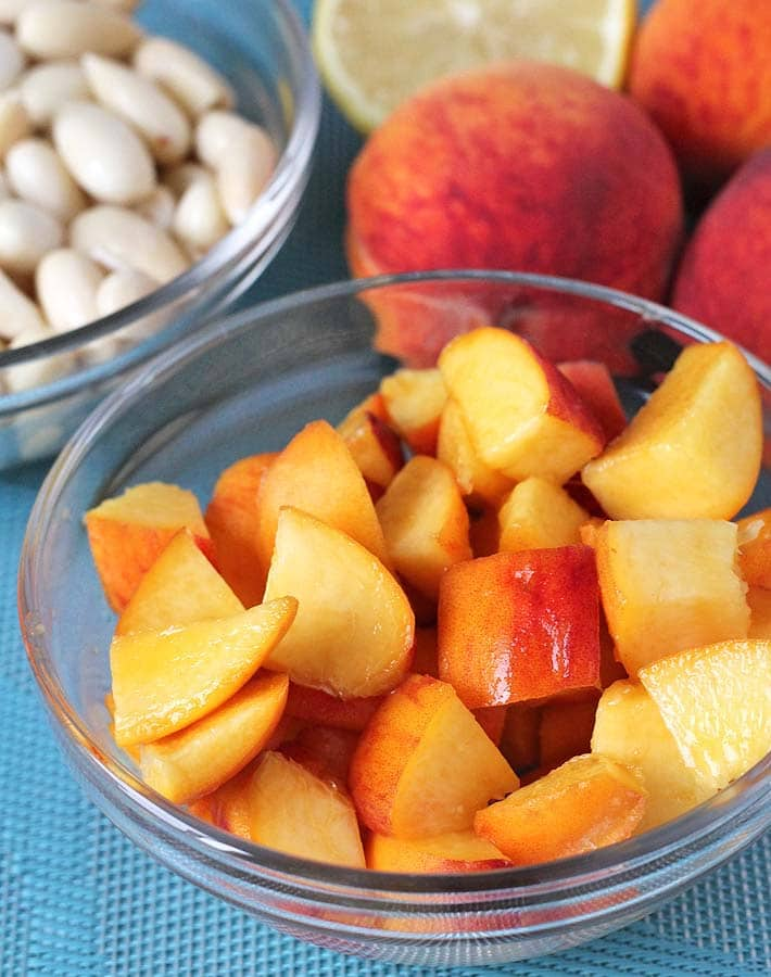Some of the ingredients for No Bake Peach Cheesecake bites on a table (fresh peaches, almonds, lemon)