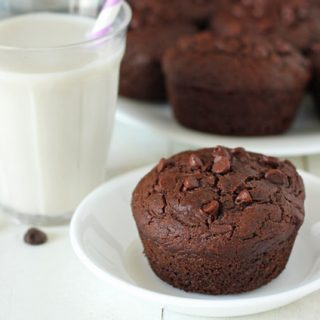 Vegan Gluten Free Chocolate Zucchini Muffins on a plate, a glass on almond milk with a straw in it sits behind the plate.