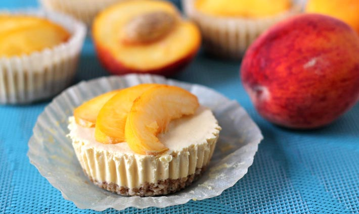 A No Bake Peach Cheesecake bite on a table with it wrapper peeled down.