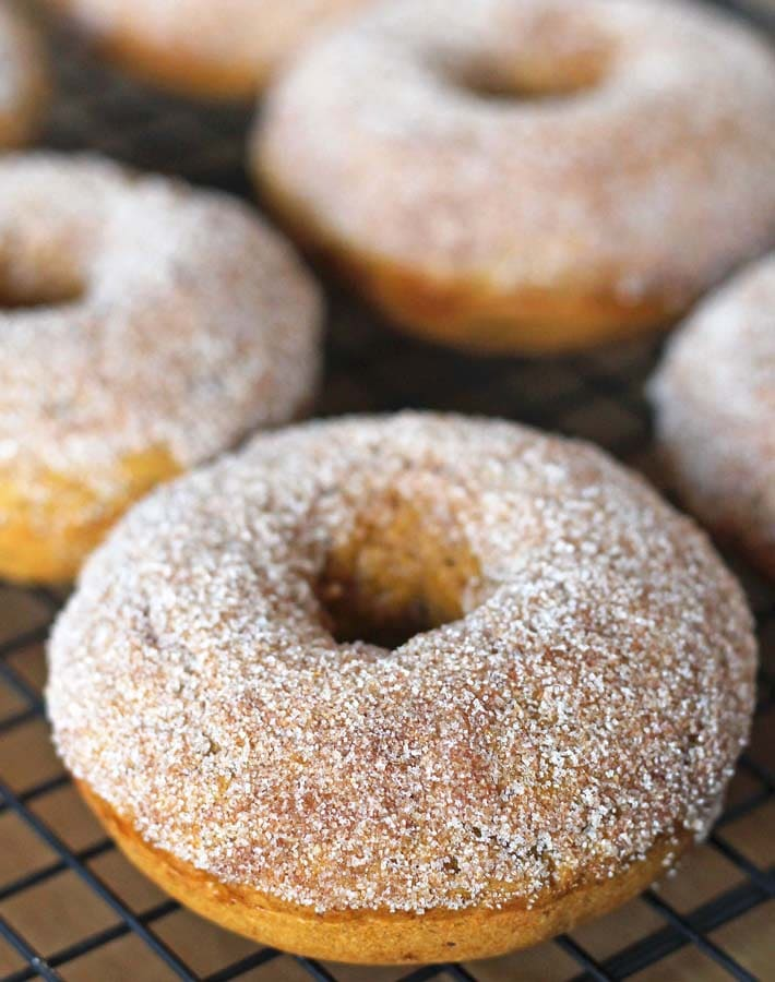 Vegan Baked Pumpkin Doughnuts on a cooling rack, doughnuts have been dusted with sugar.