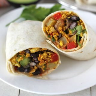 Tofu Breakfast Burritos on a plate cut in half.