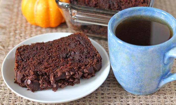 A slice of Chocolate Pumpkin Bread on a white plate with a blue mug filled with tea to the right.