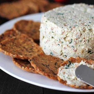 Close up shot of garlic herb vegan almond cheese spread onto a cracker.