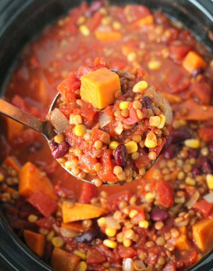 An up close shot of a ladle full of Lentil Sweet Potato Chili over the slow cooker it came from.
