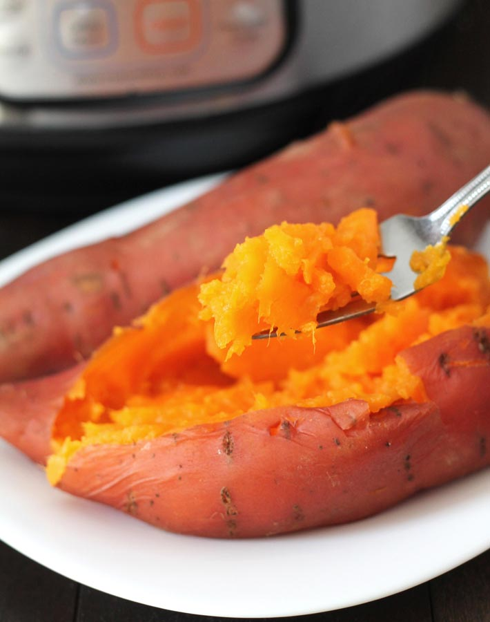 Easy Instant Pot Vegan Recipes - A fork holding a scoop of Instant Pot Sweet Potatoes to show the texture.