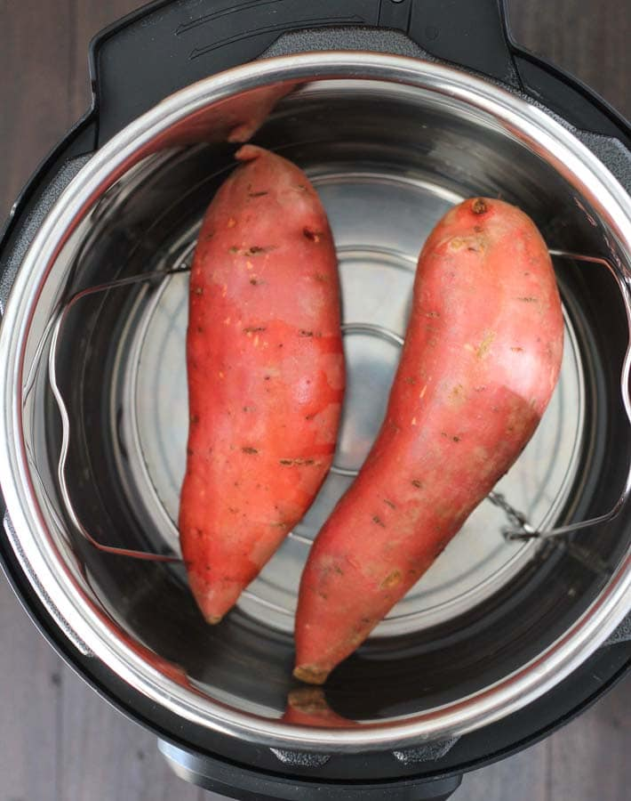 Two raw sweet potatoes in an Instant Pot to make Instant Pot Sweet Potatoes.