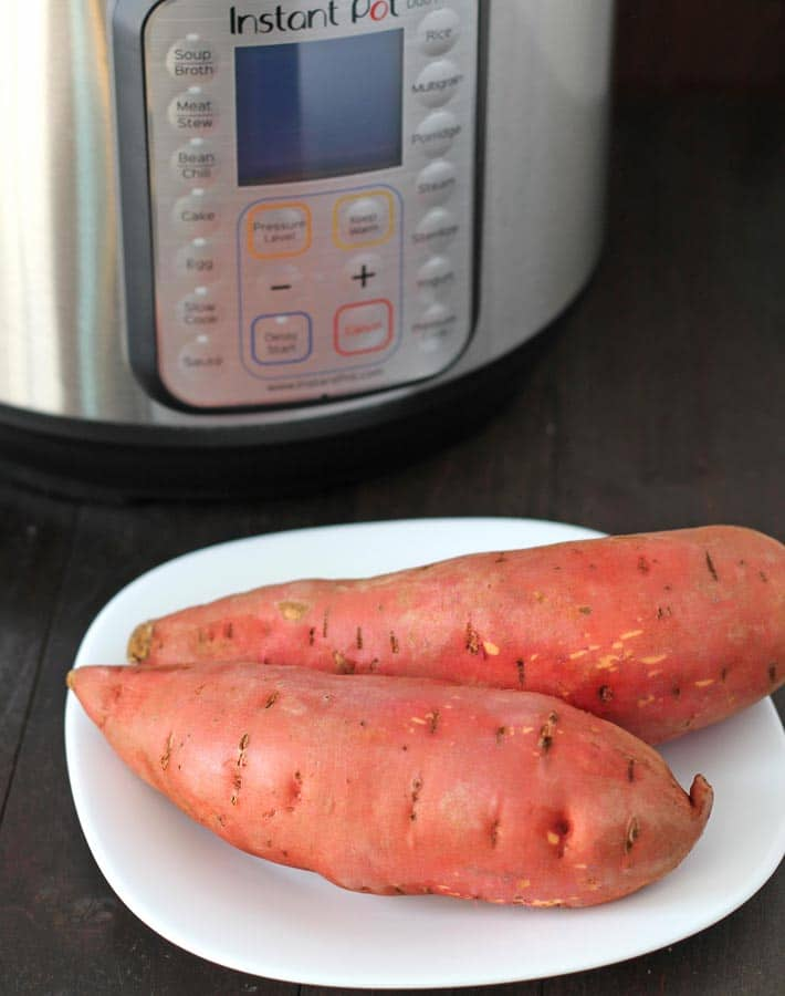 Two raw sweet potatoes on a plate to make Instant Pot Sweet Potatoes.