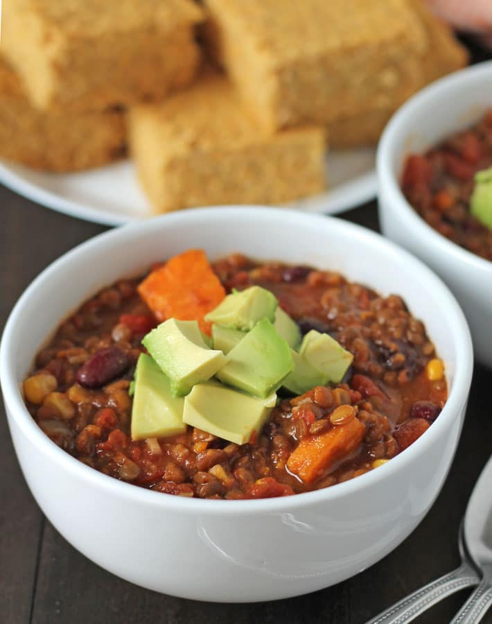 Lentil Sweet Potato Chili topped with diced avocado in a white bowl.