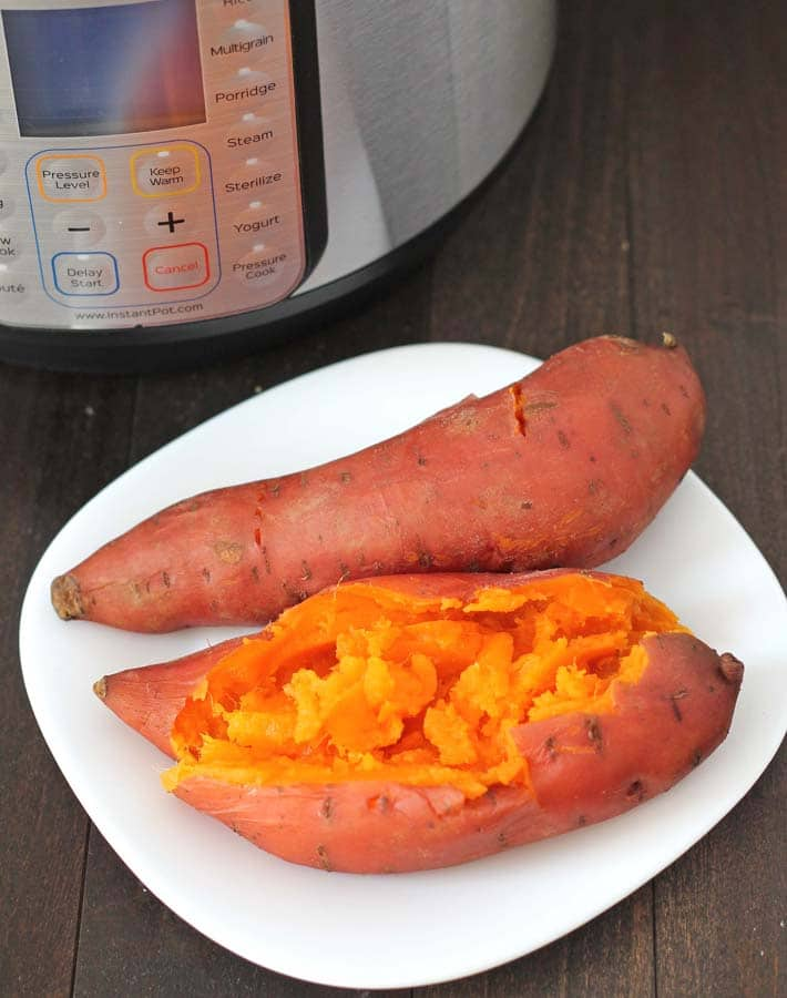 Two Instant Pot Sweet Potatoes on a white plate, one potatoe has been split open to show the inside.