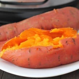 Close up shot of two Instant Pot Sweet Potatoes on a white plate.