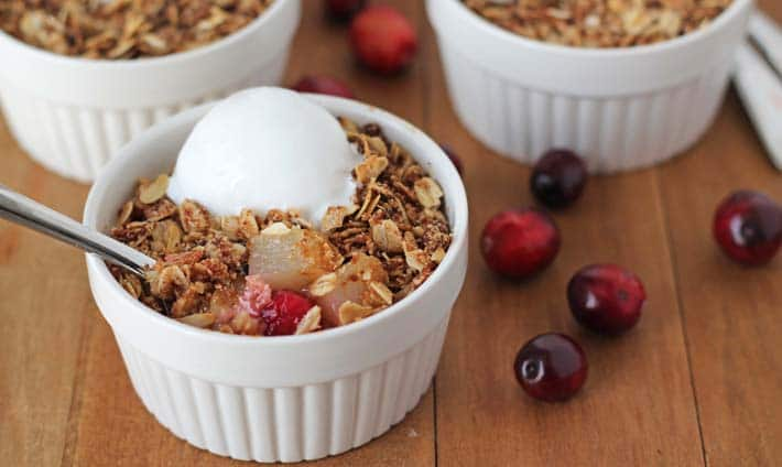 Pear Cranberry Crisp in a ramekin on a brown table.