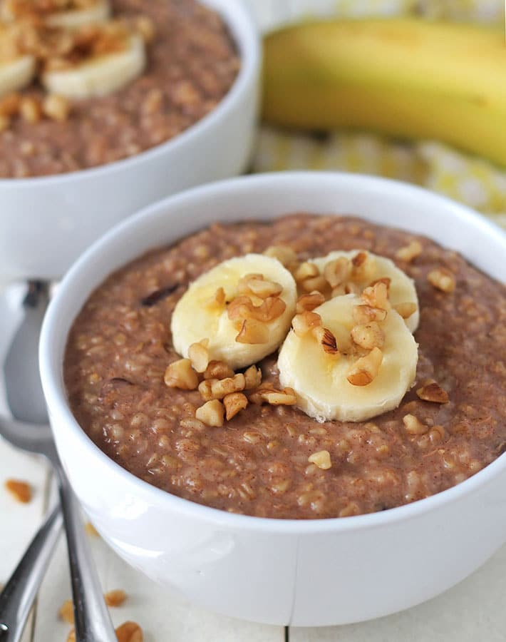 Easy Instant Pot Vegan Recipes - Two bowls of Banana Steel Cut Oats in white bowls on a white table.