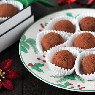 Dark Chocolate Mint Truffles on a holiday plate sitting on a dark wood table.