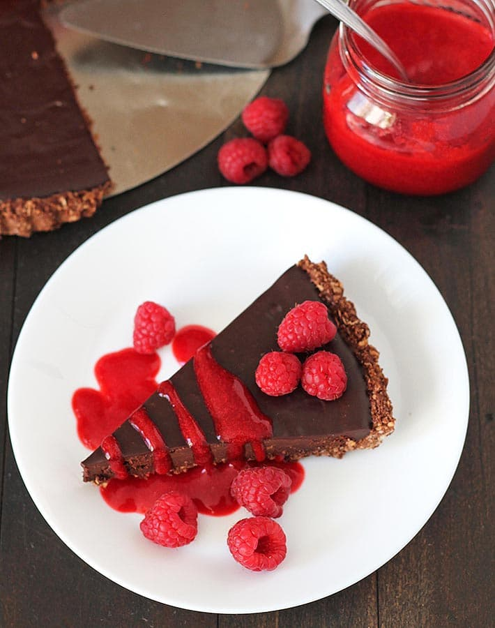 Overhead shot of a slice of vegan chocolate tart on a white plate, a jar of raspberry sauce sits behind the plate.