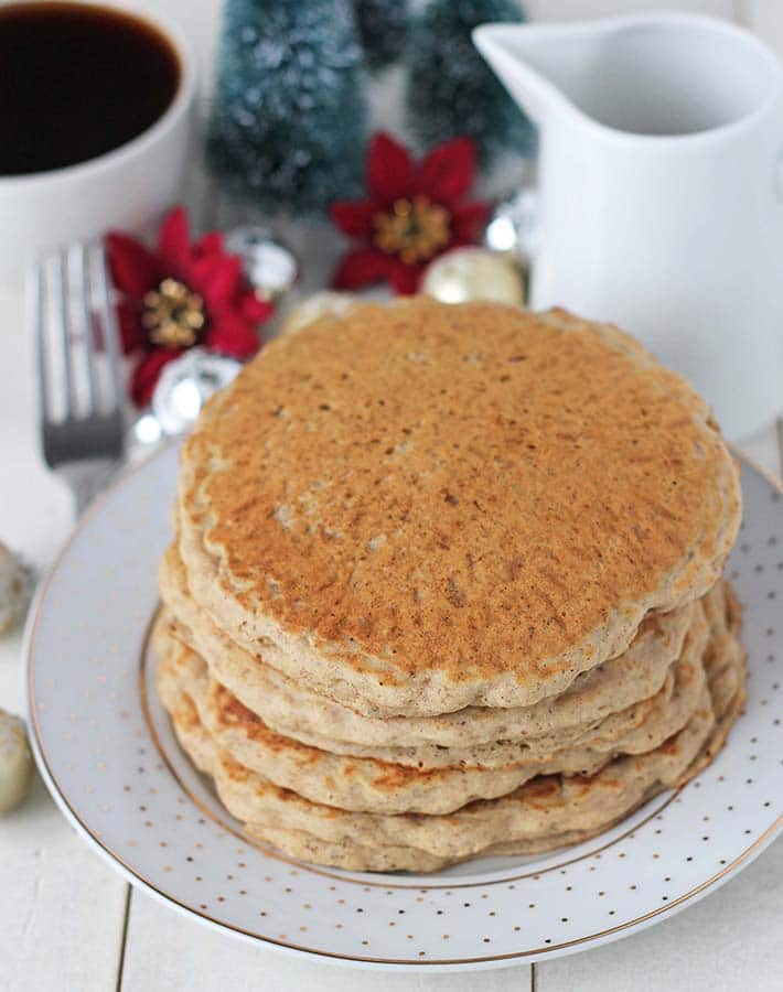 Four gluten free vegan pancakes on a holiday plate, a cup of coffee and Christmas decorations sit behind.